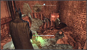Jump over the small wall and look for a fragile wall fragment nearby the Trophy #1 - Batman trophies (17-25) | Industrial District - Industrial District - Batman: Arkham City Game Guide