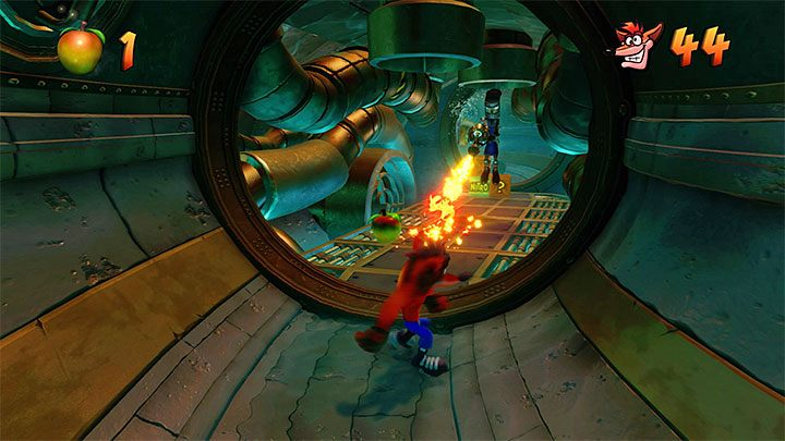 After the stage starts, walk around the nitroglycerine crate and the robots - Sewer or Later | Crash Bandicoot 2 | Levels - Crash Bandicoot 2 - Sewer Warp Room - Crash Bandicoot N. Sane Trilogy Game Guide
