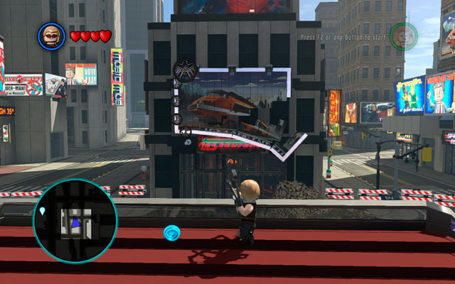 At the beginning of the stage approach to the balustrade as Hawkeye and detonate all silver elements surrounding a billboard at the opposite side of the huge hole - Times Square / Oscorp - Walkthrough - LEGO Marvel Super Heroes - Game Guide and Walkthrough