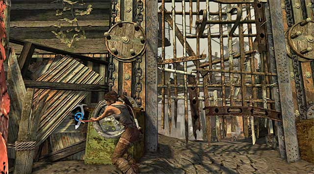 Approach the left gate mechanism and use the climbing axe (tap the action button) to unlock access to the southern area of the town, and a new base camp (Ancient Gate) (reward: 100 XP) - Reach the Gate Under the Bridge | 14: Highway to Hell Walkthrough - 14: Highway to Hell | Walkthrough - Tomb Raider Game Guide